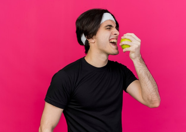 Young sporty man wearing sportswear and headband holding green apple biting it