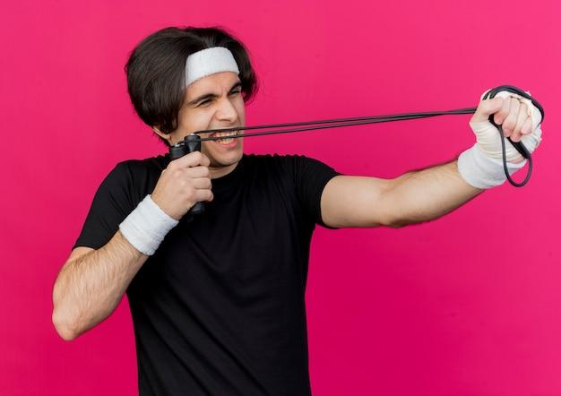 Giovane uomo sportivo che indossa abbigliamento sportivo e fascia tenendo la corda per saltare che mira con esso