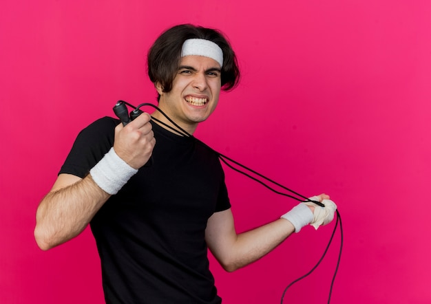 Giovane uomo sportivo che indossa abbigliamento sportivo e fascia tenendo la corda per saltare scontento dell'espressione infastidita