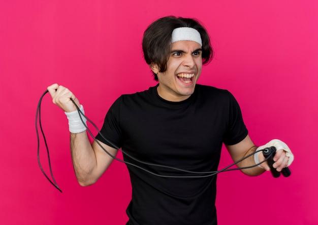 Giovane uomo sportivo che indossa abiti sportivi e fascia tenendo la corda per saltare andando a lanciarlo