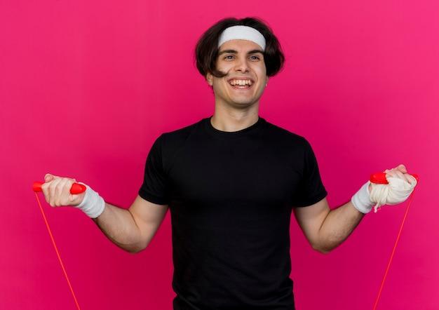 Giovane uomo sportivo che indossa abiti sportivi e fascia tenendo la corda per saltare saltando felice ed emozionato sorridendo allegramente