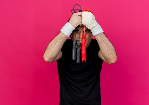 Giovane uomo sportivo che indossa abbigliamento sportivo e fascia tenendo le corde per saltare cercando confuso e scontento
