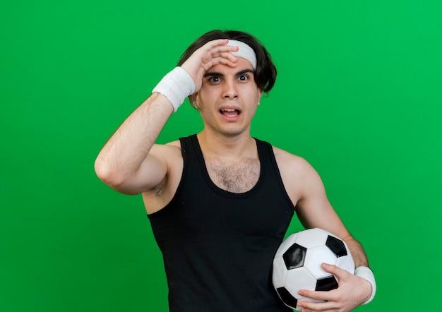 Giovane uomo sportivo che indossa abbigliamento sportivo e fascia tenendo il pallone da calcio essendo confuso con la mano sopra la testa