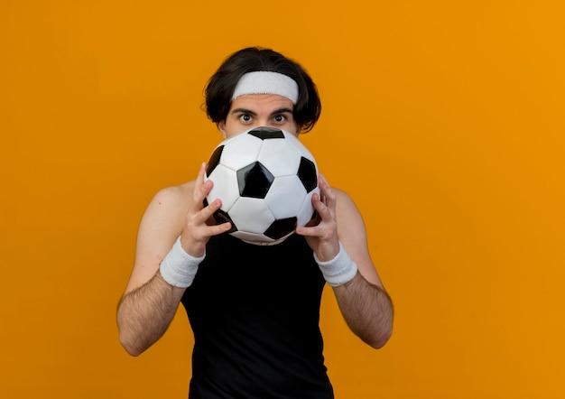 Giovane uomo sportivo che indossa abbigliamento sportivo e fascia che tiene il pallone da calcio che nasconde la sua faccia in piedi