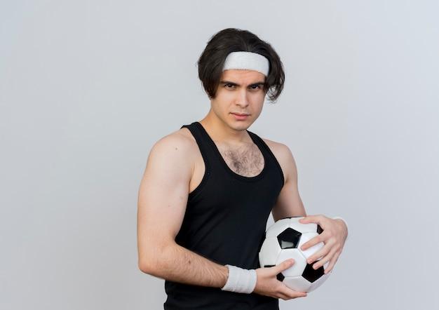 Giovane uomo sportivo che indossa abbigliamento sportivo e fascia tenendo il pallone da calcio guardando la parte anteriore con la faccia seria in piedi sopra il muro bianco