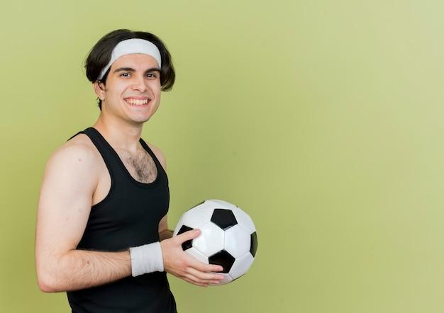 Giovane uomo sportivo che indossa abbigliamento sportivo e fascia che tiene in mano un pallone da calcio che sembra sorridente con la faccia felice in piedi