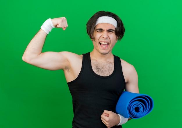 Giovane uomo sportivo che indossa abbigliamento sportivo e fascia che tiene materassino yoga alzando il pugno teso e fiducioso