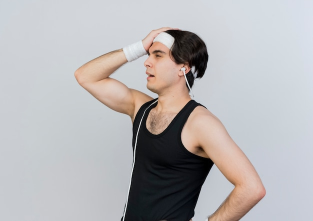 Young sporty man wearing sportswear and headband looking aside with hand on his head being confused standing over white wall