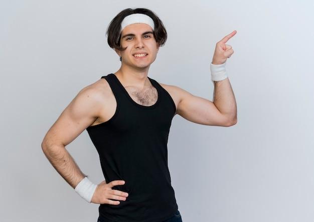 Giovane uomo sportivo che indossa abbigliamento sportivo e fascia guardando la parte anteriore sorridente fiducioso che punta con il dito indice a lato in piedi sopra il muro bianco