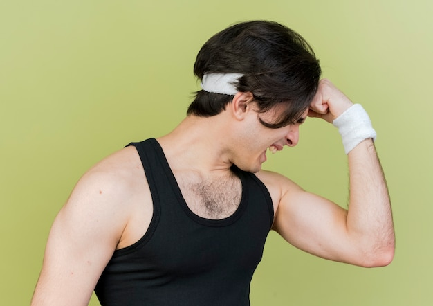 Young sporty man wearing sportswear and headband raising fist showing biceps looking strained