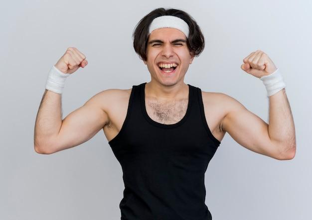 Giovane uomo sportivo che indossa abbigliamento sportivo e fascia alzando i pugni che mostrano forza e bicipiti che sembrano tesi felici e positivi