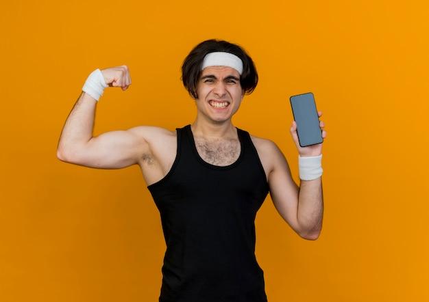 Giovane uomo sportivo che indossa abbigliamento sportivo e fascia che mostra lo smartphone che alza il pugno che mostra i bicipiti che sembrano tesi