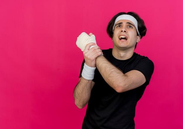 Giovane uomo sportivo che indossa abbigliamento sportivo e fascia che tocca il suo polso fasciato che soffre di dolore