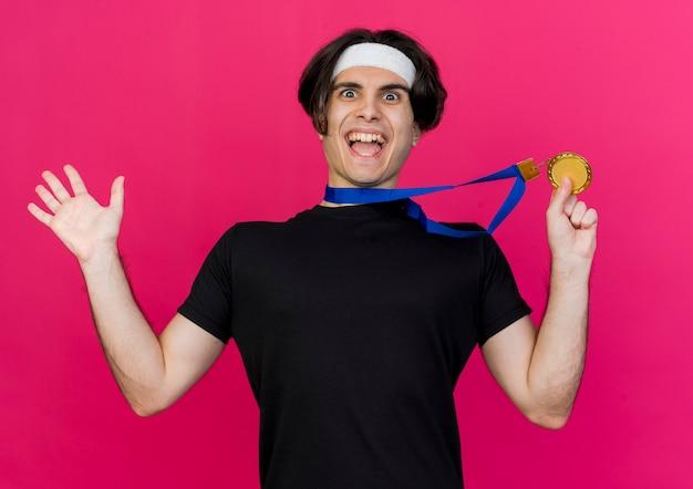Giovane uomo sportivo che indossa abbigliamento sportivo e fascia con medaglia d'oro al collo che mostra la sua medaglia felice ed emozionata
