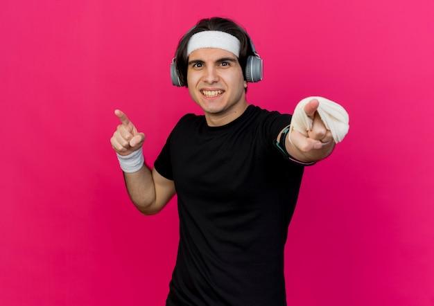 Giovane uomo sportivo che indossa abbigliamento sportivo e fascia con auricolari e fascia da braccio dello smartphone che punta alla telecamera tesa e sicura