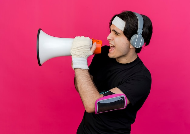 Young sporty man wearing sportswear and headband with heaphones and smartphone armband shouting to megaphone