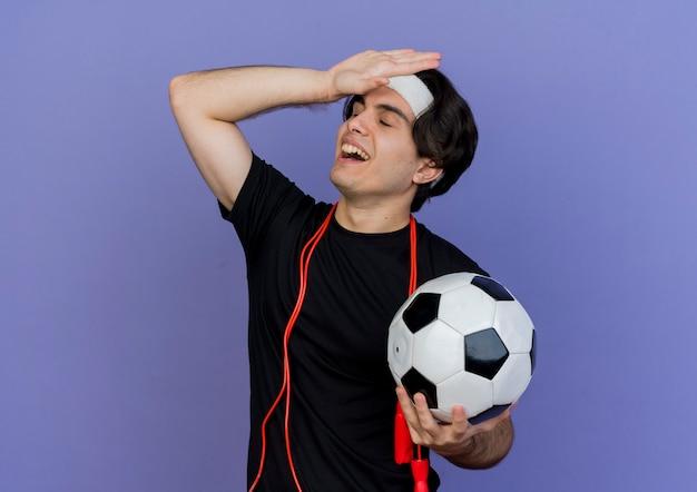 Giovane uomo sportivo che indossa abbigliamento sportivo e fascia per saltare con la corda intorno al collo tenendo il pallone da calcio cercando confuso con la mano sulla sua testa per errore