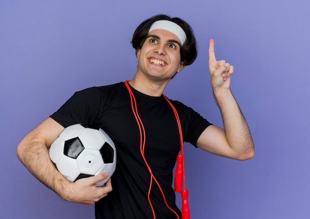 Young sporty man wearing sportswear and headband with skipping rope around neck holding soccer ball pointign up with finger smiling having new idea