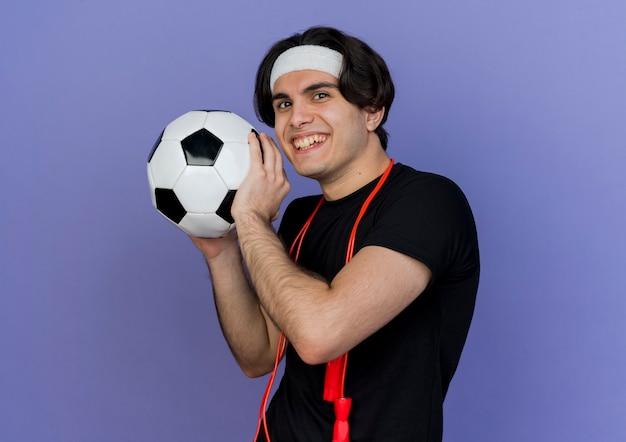 Giovane uomo sportivo che indossa abbigliamento sportivo e fascia con corda per saltare intorno al collo tenendo il pallone da calcio sorridente con la faccia felice