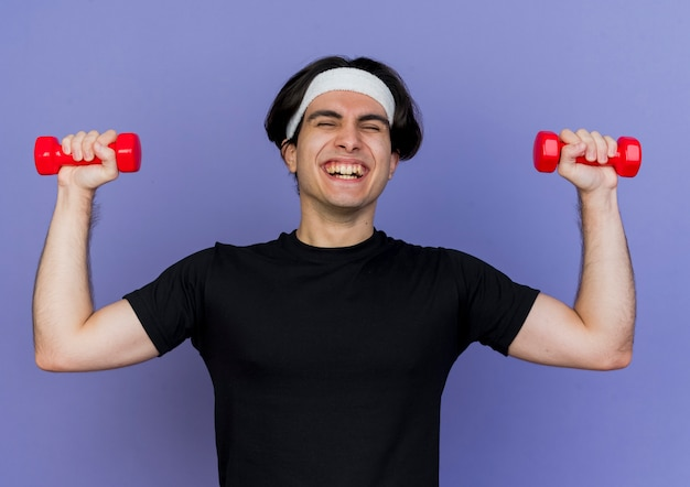 Young sporty man wearing sportswear and headband working out with dumbbells happy and excited smiling cheerfully