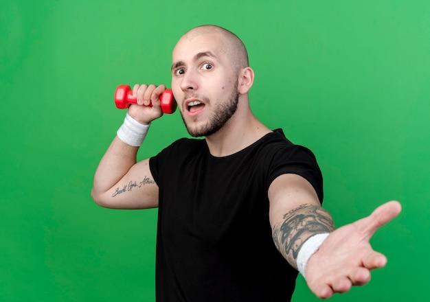 ダンベルを保持し、緑の壁で隔離の手を差し出すリストバンドを身に着けている若いスポーティな男