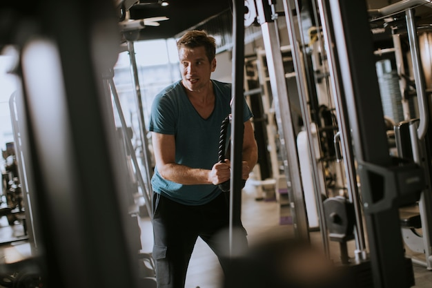 Young sporty man working out on pull-down machine in gym