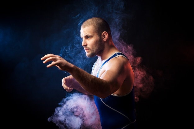 A young sporty man wrestler in a green sports shirt and blue wrestling tights  posing against a blue and red vape smoke background on a black isolated