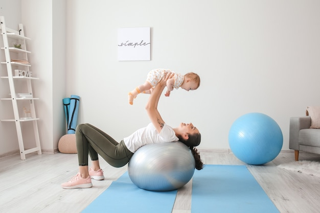 Молодая спортивная мать и ее ребенок делают упражнения с фитболом дома
