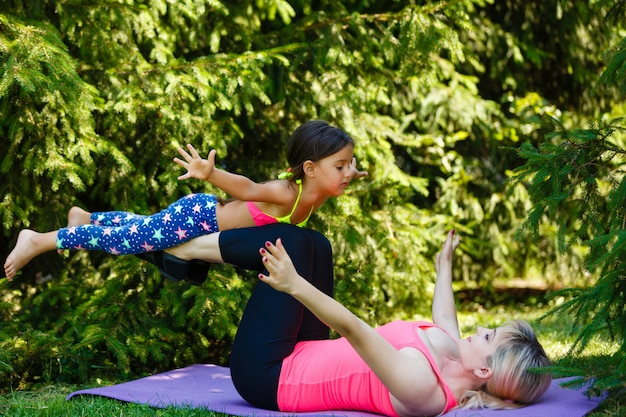 Young sporty mother and cute little daughter doing yoga exercises on grass in the park