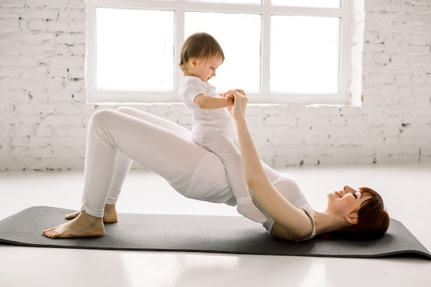 Young sporty mother does physical yoga or pilates exercises, butt bridge, together with her baby against big windows background. fitness, happy maternity