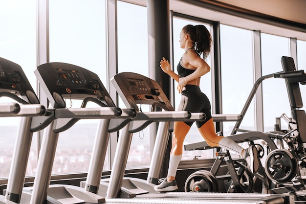 Young sporty muscular brunette with ponytail running on treadmill. backs turned, full length. pain is nothing compared to what it feels like to quit.