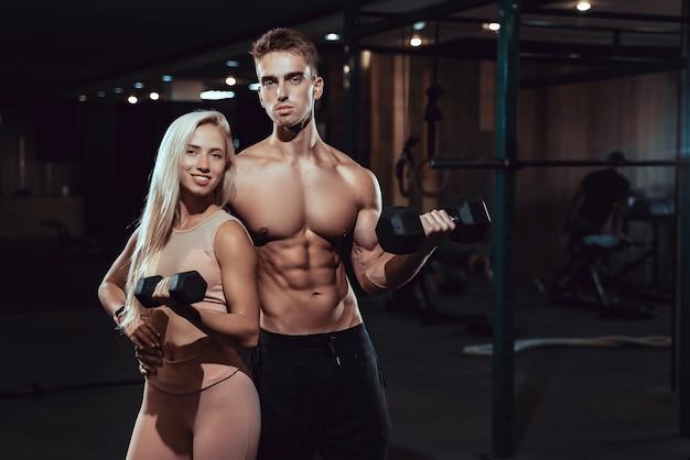 체육관에서 근육과 운동을 보여주는 젊은 스포티 한 섹시 커플. 근육질의 남자와 여자.