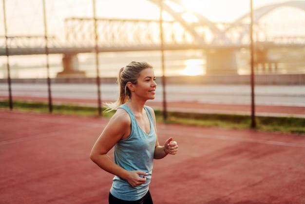 仕事の前に夏の朝早くジョギングする若いスポーティなスリムなブロンドの女の子。