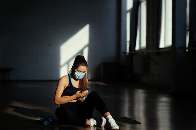 Young sporty woman after practicing yoga, break in doing exercise, relaxing on yoga mat