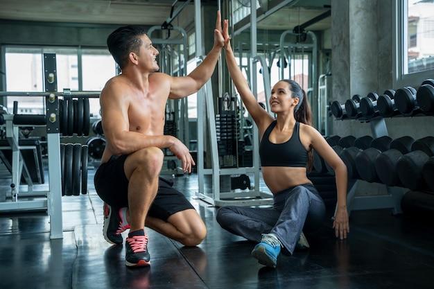 Молодая sporty женщина и человек давая друг другу максимум 5 после тренировки на спортзале, тренировки фитнеса и здоровой концепции.