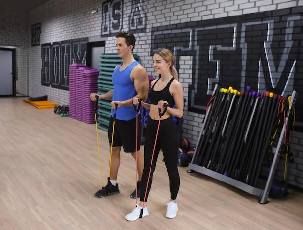 Молодая спортивная женщина и мужчина тренируются в современном тренажерном зале