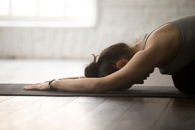 Young sporty woman in balasana pose, white loft studio, closeup