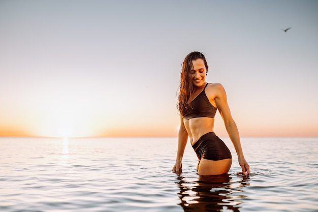 Young sporty woman in calm sea at sunset in black sportswear. space for message.