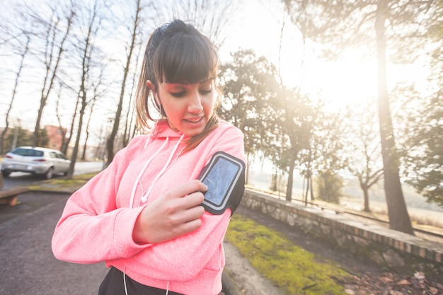 Young sporty woman checking smart phone during workout
