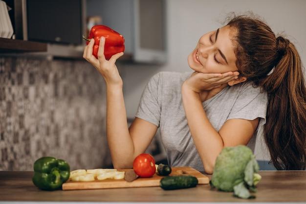 Молодая спортивная женщина готовит на кухне