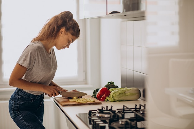 Young sporty woman cooking at the kitchen