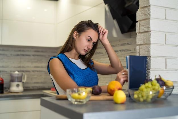 キッチンの木製テーブルで新鮮なさまざまな果物を切る若いスポーティな女性。健康食品