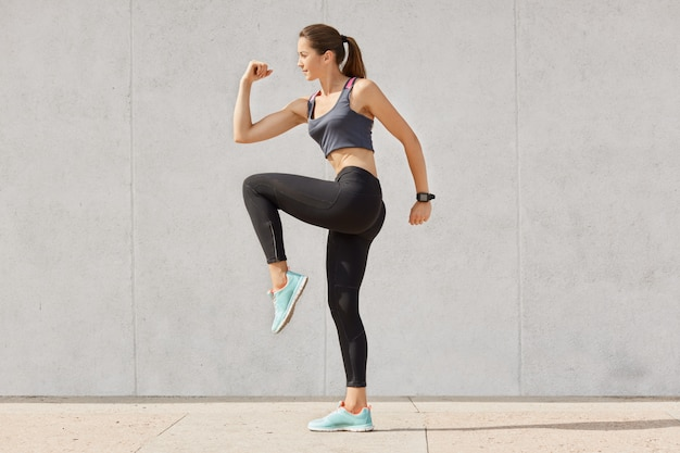 Young sporty woman doing exercise against gray