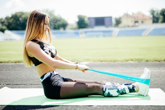 Young sporty woman doing exercises with rubber band outdoor at stadium track.