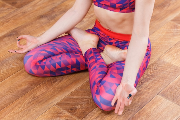 Young sporty woman doing padmasana exercise
