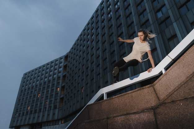 Young sporty woman doing parkour in city