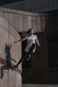 市でパルクールをしている若いスポーティな女性。フリーランニングをしている少女。