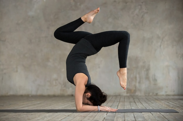 Young sporty woman doing pincha mayurasana exercise