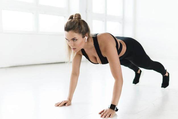 ジムで体操中に腕立て伏せをしている若いスポーティな女性