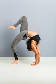 Молодая спортивная женщина делает позы художественной гимнастики